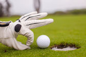 Golf player man pushing golfball into the hole — Stock Photo