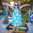 Little beautiful girl in a boat on the beach at exotic resort — Stock Photo