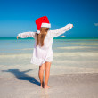 Back view of Little cute girl in red hat santa claus on the beach — Stock Photo