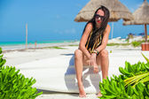 Young sexy woman sitting on a boat in white sandy beach — Stockfoto