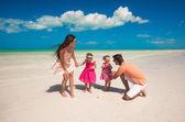 ビーチで楽しんで 2 人の娘と若い美しい家族 — ストック写真
