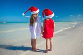 Back view of Little cute girlsin Christmas hats on the exotic beach — Photo