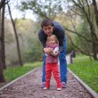 Little girl with young dad in park at warm autumn day — Stock Photo #37072593