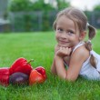 Little girl in garden with a plate of vegetables — Stock Photo