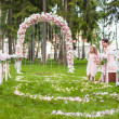 Wedding benches with guests and flower arch for ceremony outdoors — Stock Photo #37073211