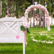 Wedding benches and flower arch for ceremony outdoors — Stock Photo