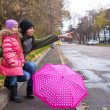 Little girl and her ​​mother walking with umbrella on a rainy day — Stock Photo