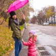 Little girl walking with her ​​mother under an umbrella on a rainy day — Stock Photo