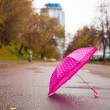 Pink children's umbrella on the wet asphalt outdoors — Stock Photo