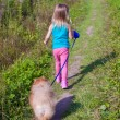 Little girl walking with her ​​dog on a leash — Stock Photo