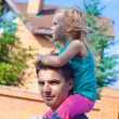 Little girl riding on young dad outdoors — Stock Photo