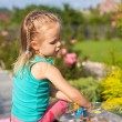 Little cute girl playing with toys in the yard — Stock Photo