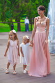 Two adorable girls with their mother outdoor at wedding — Stock Photo