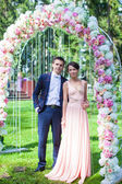 Lovely young couple in a flower arch at the wedding ceremony — Stock Photo