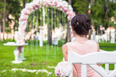 Back view of beautiful young woman in a long dress at the ceremony outdoors — Stock Photo