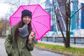 Young woman walking with umbrella in autumn rainy day — Stock Photo
