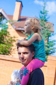 Niña cabalgando sobre el joven papá al aire libre — Foto de Stock