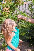 小女孩从妈妈樱桃的手打开她的嘴和渔获量 — 图库照片