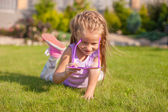 Adorable little girl with Happy Birthday glasses smiling outdoor — Stock Photo