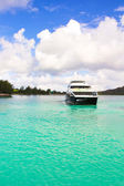 Небольшие лодки и крейсер у побережья на тропический остров в бирюзовой воде — Стоковое фото