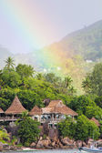 Rainbow over tropical island and luxurious hotel — Stock Photo