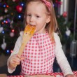 Little girl eating the dough for ginger cookies in kitchen — Stock Photo