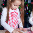 Little beautiful girl making cakes from the molds for Christmas — Stock Photo