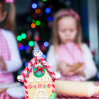 Gingerbread fairy house decorated by colorful candies on a background of little girl — Stock Photo #37423911