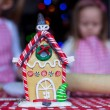 Gingerbread fairy house decorated by colorful candies on a background of little girls — Stock Photo