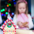 Gingerbread fairy house decorated by colorful candies on a background of little girl — Stock Photo #37423977