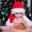 Adorable little girl in Santa hat eating the dough for ginger cookies — Stock Photo