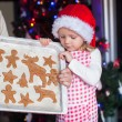 Little girl in Santa hat shows her Christmas gingerbread cookies — Stock Photo #37424469
