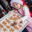 Little girl in Santa hat shows her Christmas gingerbread cookies — Stock Photo #37424535