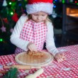 Adorable little girl eating the dough for ginger cookies in kitchen — Stock Photo