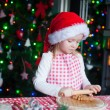 Adorable little girl in Santa hat baking gingerbread cookies for Christmas — Stock Photo