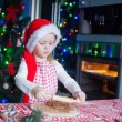 Little cute girl in Santa hat bake gingerbread cookies for Christmas — Stock Photo