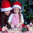 Happy mom and little girl in Santa hat baking Christmas gingerbread cookies together — Stock Photo