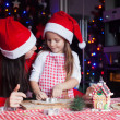 Adorable little girl with mother wearing santa hats baking Christmas gingerbread cookies together — Stock Photo