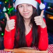 Young woman in Christmas hat raised thumbs up at home — Stock Photo