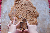 Child hands making from dough gingerbread man — Stock Photo
