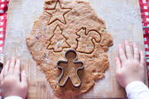 Child hands making from dough gingerbread man for Christmas — Stock Photo