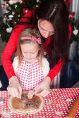 Little girl with young mother baking Christmas gingerbread cookies together — Stock Photo