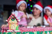 幸せな家族の背景にカラフルなキャンディーで飾られたジンジャーブレッドの妖精の家 — ストック写真