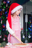 Adorable little girl with rolling pin baking gingerbread cookies for Christmas — Foto de Stock