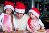 Little girls with young dad in Santa hat bake Christmas gingerbread cookies — Stock Photo
