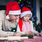 Young dad with little daughter in Santa hat bake Christmas gingerbread cookies — Stock Photo