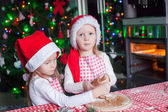 Little girls baking gingerbread cookies for Christmas in Santa hat — ストック写真