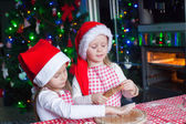 Little cute girls in Santa hats bake gingerbread cookies for Christmas — ストック写真