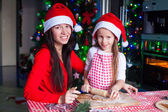Happy family in Santa hats baking Christmas gingerbread cookies together — ストック写真