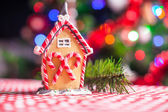 Close-up Gingerbread fairy house decorated by colorful candies on a background of bright Christmas tree with garland — Stock Photo